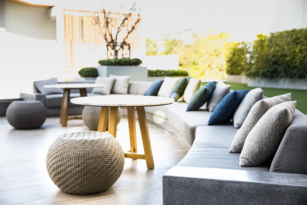 Big comfort cushion sofa with cozy pillows and the marble stone table and the round wicker chairs at the pool side.